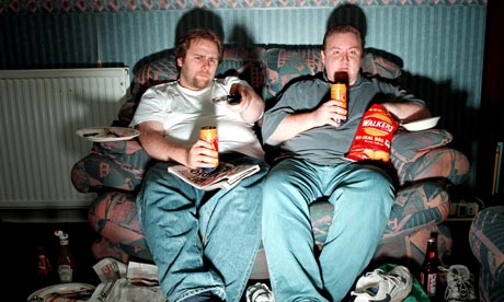 Men lounge on sofa watching TV